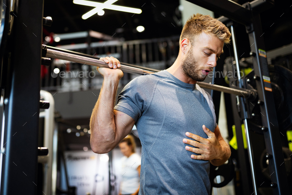 Young handsome man doing exercises in gym - Stock Photo - Images