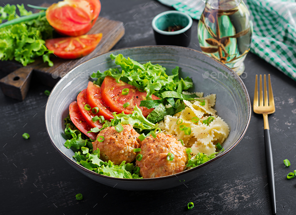 Italian pasta. Farfalle with meatballs and salad on dark background. Dinner. Slow food concept - Stock Photo - Images