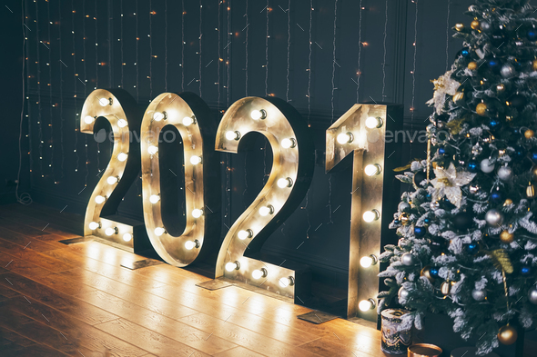 Glowing numbers 2021 on a dark wall background, decorated Christmas tree - Stock Photo - Images