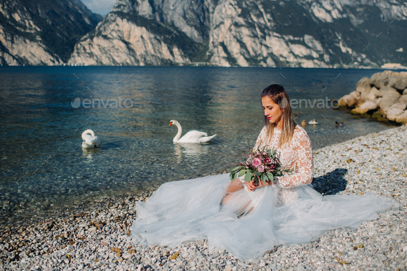 a girl in a smart white dress is sitting on the embankment of lake Garda.A woman is photographed - Stock Photo - Images