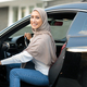 Cheerful smiling muslim lady driving her new car - PhotoDune Item for Sale