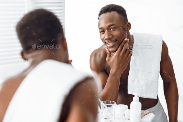 Black Guy Touching Well-Shaved Face Caring For Skin In Bathroom - Stock Photo - Images