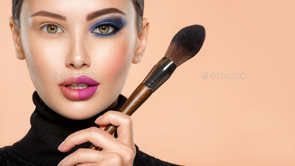 Portrait of a girl with cosmetic brush near face. - Stock Photo - Images