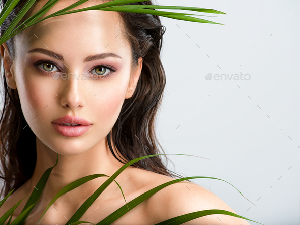 Young beautiful woman with healthy skin of face and palm leaves. - Stock Photo - Images