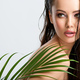 Young beautiful woman with healthy skin of face and palm leaves. - PhotoDune Item for Sale