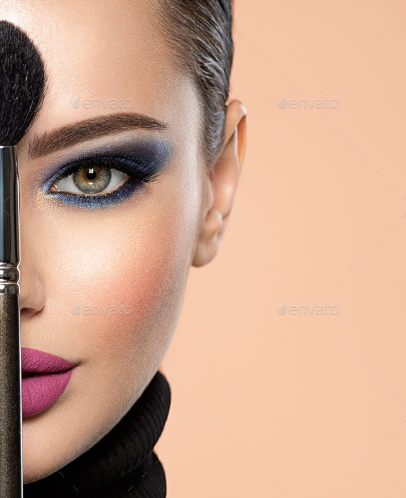 Portrait of a girl with cosmetic brush at face. Woman holds a big makeup brush right in the middle - Stock Photo - Images