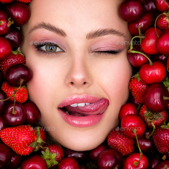 Young, winking girl with bright makeup and a berry background. - Stock Photo - Images