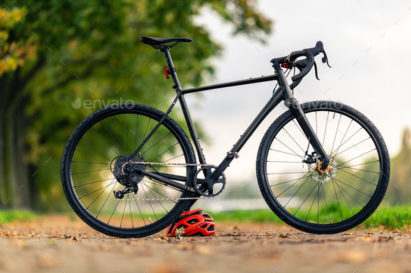 Road gravel bicycle on city street under trees - Stock Photo - Images