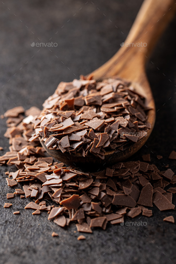 Grated dark chocolate. Chocolate flakes in wooden spoon. - Stock Photo - Images