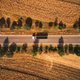 Top view aerial photo of truck on the road through plain landscape countryside - PhotoDune Item for Sale