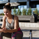 Outdoor shot of young female athlete sitting on a bench and looking at smartphone, resting after - PhotoDune Item for Sale