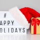 Lightbox with happy holidays hashtag text, Santa hat and gift box - PhotoDune Item for Sale