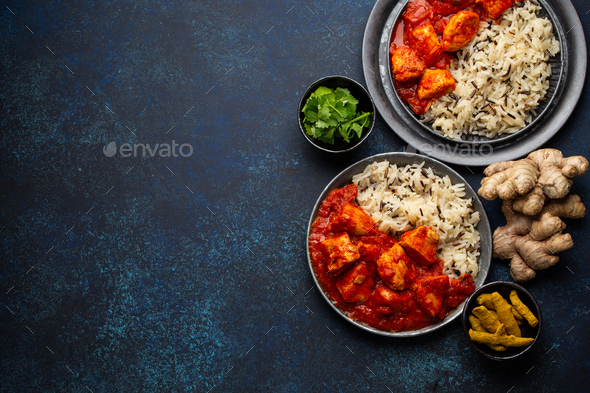Chicken tikka masala dish with rice, flat Indian bread and spices in rustic metal plates - Stock Photo - Images