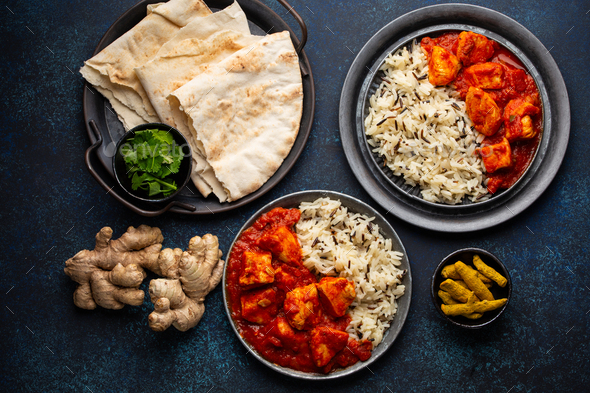 Chicken tikka masala dish with rice, flat Indian bread and spices - Stock Photo - Images