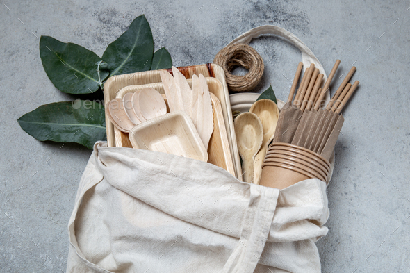 Eco craft paper and wooden tableware. Paper cups, dishes, bag, plates and wooden cutlery in linen - Stock Photo - Images