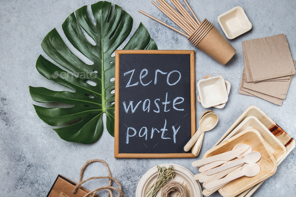 Zero waste party concept. Eco ffriendly tableware, craft bags and monstera leaves on gray background - Stock Photo - Images