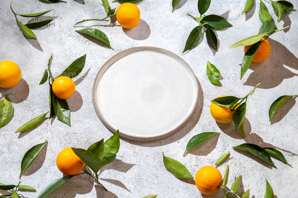 Whole oranges witl orange tree leaves on white background around empty plate. top view, flat lay - Stock Photo - Images