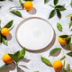 Whole oranges witl orange tree leaves on white background around empty plate. top view, flat lay - PhotoDune Item for Sale