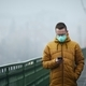 Lonely man with face mask using phone against city in fog - PhotoDune Item for Sale