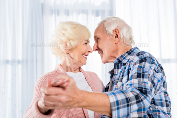 side view of smiling senior couple dancing together at home - Stock Photo - Images