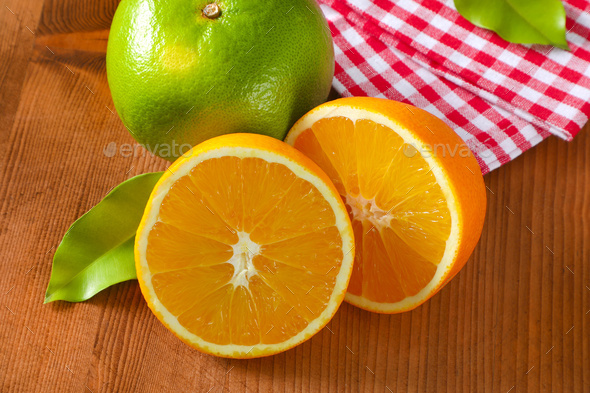 Green grapefruit and halved orange - Stock Photo - Images