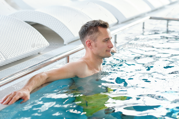 Young handsome relaxed man standing in blue transparent water of swimming pool - Stock Photo - Images