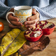Close up of autumn home indoor scene with pair of hands hold a cup of tea on a wooden table - PhotoDune Item for Sale