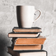 A cup of coffee on of stack of books on grey background. education, study, hobbies, read - PhotoDune Item for Sale