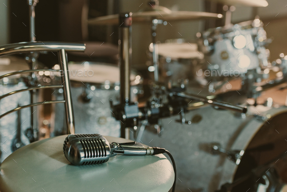 vintage microphone lying on chair in front of drum set - Stock Photo - Images