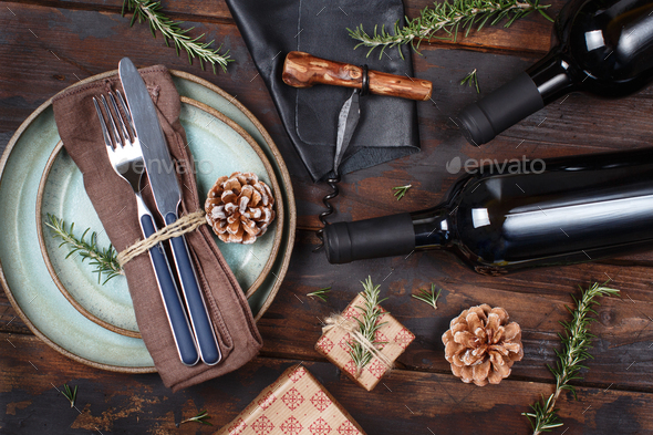 Rustic festive table setting on wooden table with wine bottles and Corkscrew - Stock Photo - Images