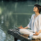 Yoga Retreat. Peaceful Young Woman Sitting in Lotus Position and Meditating by the Lake - PhotoDune Item for Sale