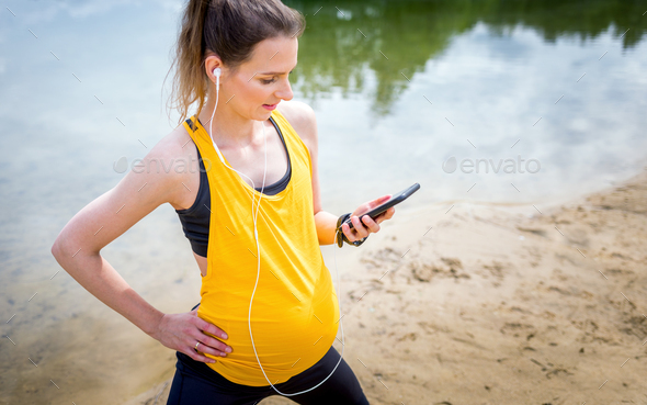 Pregnant woman using fitness app during exercises outdoor - Stock Photo - Images