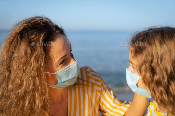 Happy mother and daughter wearing medical mask outdoor - Stock Photo - Images
