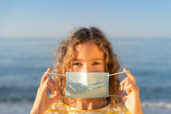Happy child wearing medical mask outdoor - Stock Photo - Images
