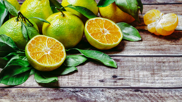 Green mandarins on wooden background, copy space - Stock Photo - Images