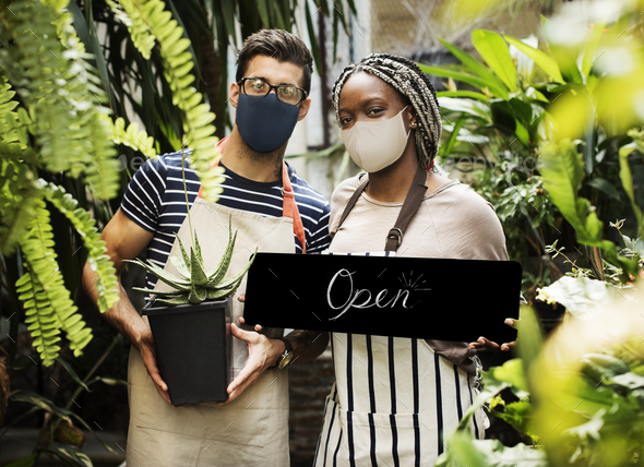Florists in face mask with open sign during new normal - Stock Photo - Images