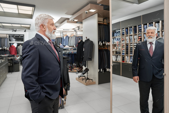 Male in stylish suit looking at mirror and estimating outfit - Stock Photo - Images