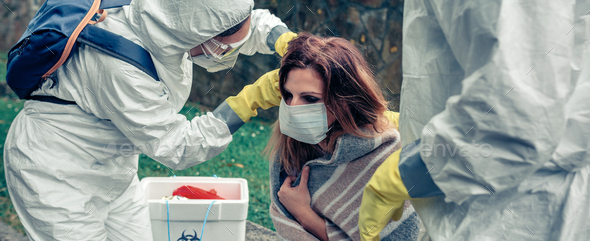 Doctors putting protective mask on woman infected with a virus - Stock Photo - Images