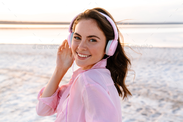 Cheery pleased young girl in sunglasses listening music - Stock Photo - Images