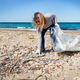 Young woman cleaning beach area from plastic bottles - PhotoDune Item for Sale