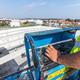 Warehouse construction. Worker on mobile elavating work platform - PhotoDune Item for Sale