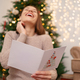 Lovely young woman reading a Christmas greeting card - PhotoDune Item for Sale