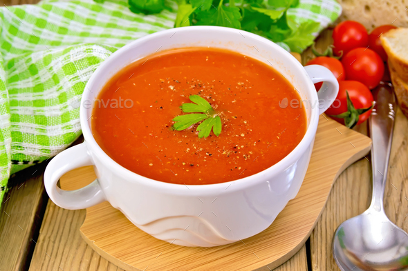 Soup tomato in bowl with spoon on board - Stock Photo - Images