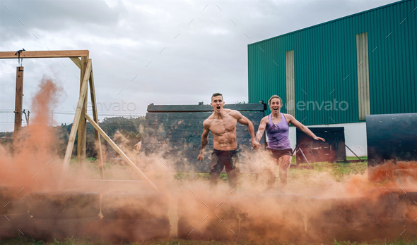 Athletes jumping finish line of an obstacle course - Stock Photo - Images