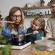 Grandma together with her daughter and granddaughter tasting Christmas dishes - PhotoDune Item for Sale