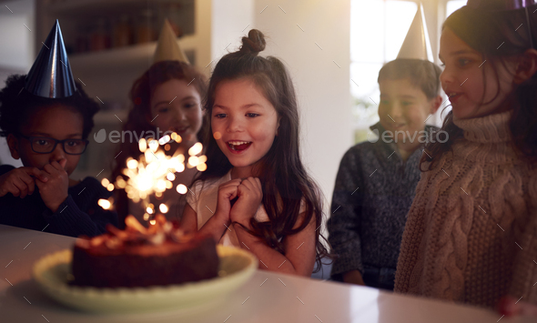 Girl Celebrating Birthday With Group Of Friends At Home Being Given Cake Decorated With Sparkler - Stock Photo - Images
