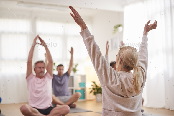 Group With Teacher Sitting On Exercise Mats Stretching In Yoga Class Inside Community Center - Stock Photo - Images