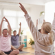 Group With Teacher Sitting On Exercise Mats Stretching In Yoga Class Inside Community Center - PhotoDune Item for Sale