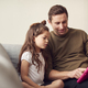 Father And Daughter Sitting On Sofa At Home Playing Together On Digital Tablet In Pink Case At Home - PhotoDune Item for Sale