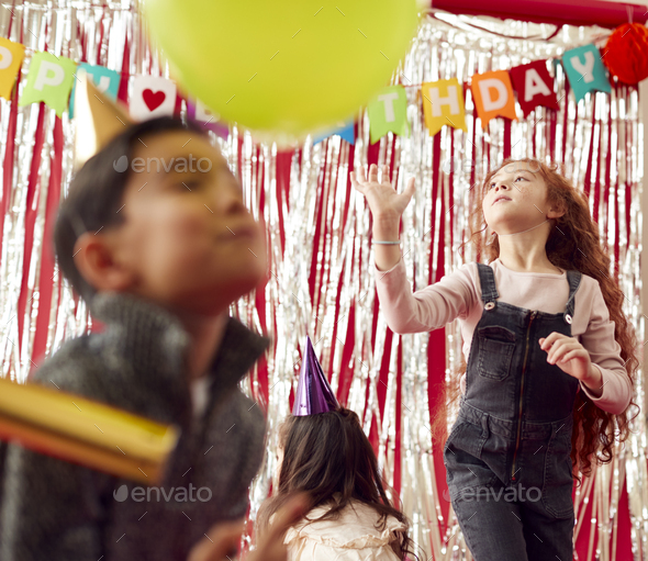 Group Of Children Celebrating At Birthday Party With Paper Hats Playing With Balloons - Stock Photo - Images